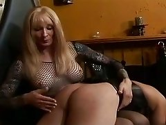 Mature blonde shemale dominates a tied up slave