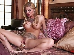 Completely tattooed blonde jams a dildo up her twat