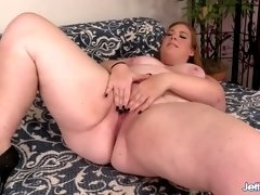 Curly Ginger Rose sits comfortably on sofa while sucking lollicock