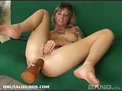 Tattooed blonde solo model jams her shaved pussy with a massive toy close up