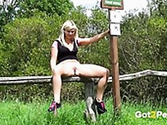 Seductive blond girlie sits on wooden stick and pisses outdoors