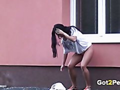 Raven haired wanton chick pissed in standing position