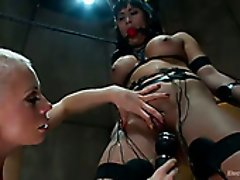 Blond seductress punishes busty brunette with ball gag in her mouth