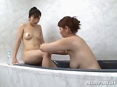 Two Japanese lesbians caress each other in a bathroom