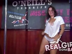 Amateur ladies on stage at the bar dance and strip for the crowd